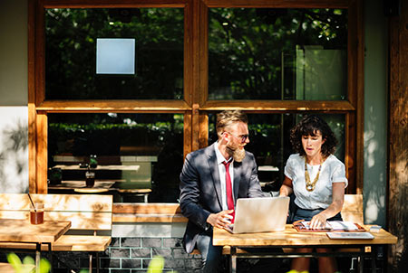 Professionally dressed man and woman meeting at a coffee shop during a business trip